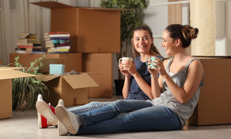 Two Happy Roommates Moving Home Resting And Talking Sitting On T